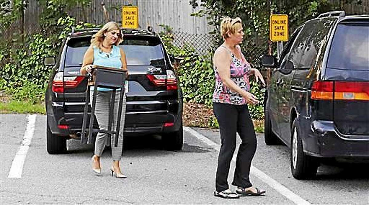 """Michele Velleman, left, carries a table, which she had just sold to Susan Locke, right, in the """"online safe zone"""" outside the police station in Georgetown, Mass., Monday, July 13, 2015. Around the nation, in police department parking lots festooned with surveillance cameras, authorities are setting up an """"online safe zones"""" where people meeting via Craigslist or buying goods via eBay can meet up without fear of assault or abduction. (AP Photo/Charles Krupa)"""