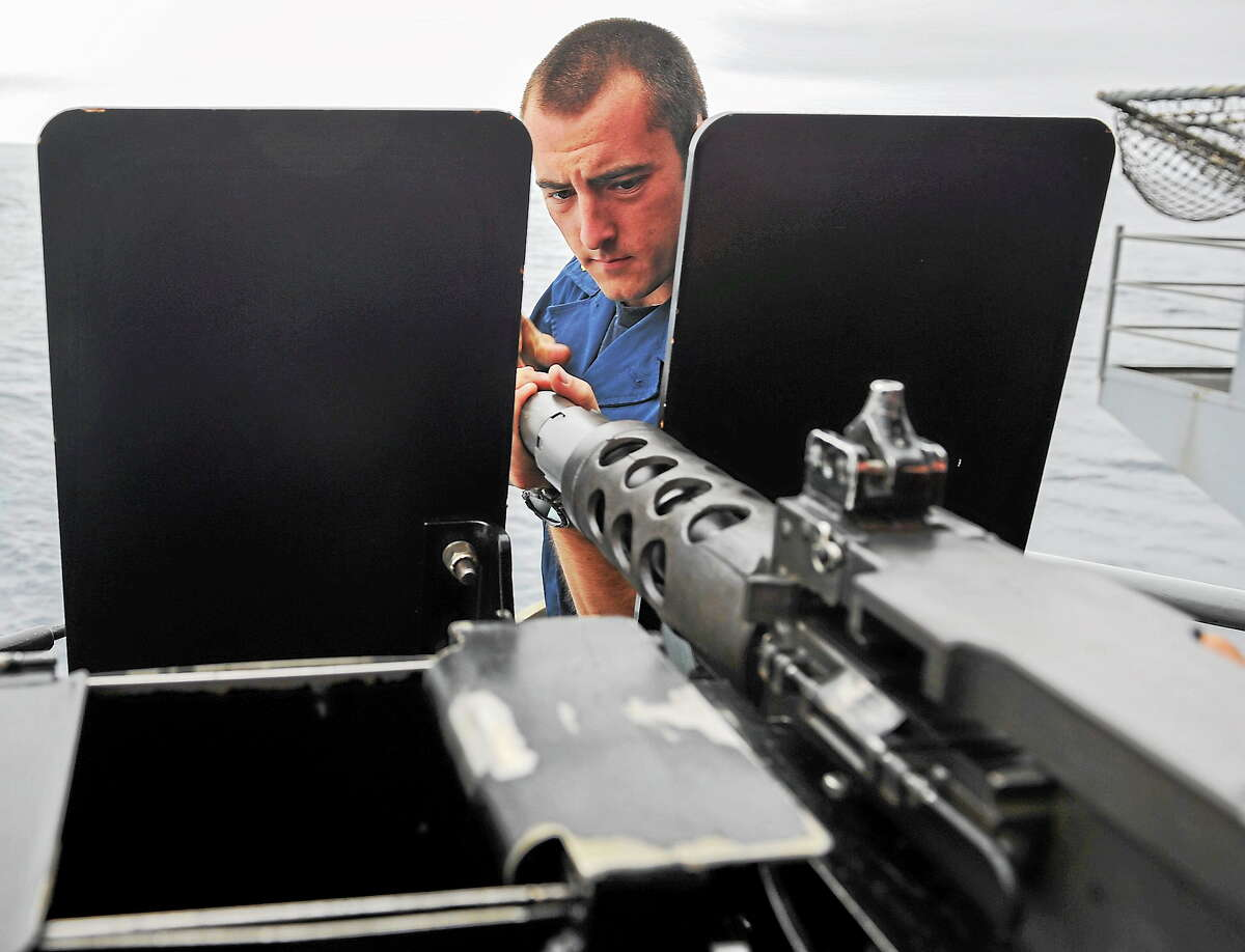 Midshipmen 2nd Class Adam M. Guy of East Hampton screws on the barrel of a .50 caliber machine gun on the fantail of the aircraft carrier USS Nimitz (CVN 68).