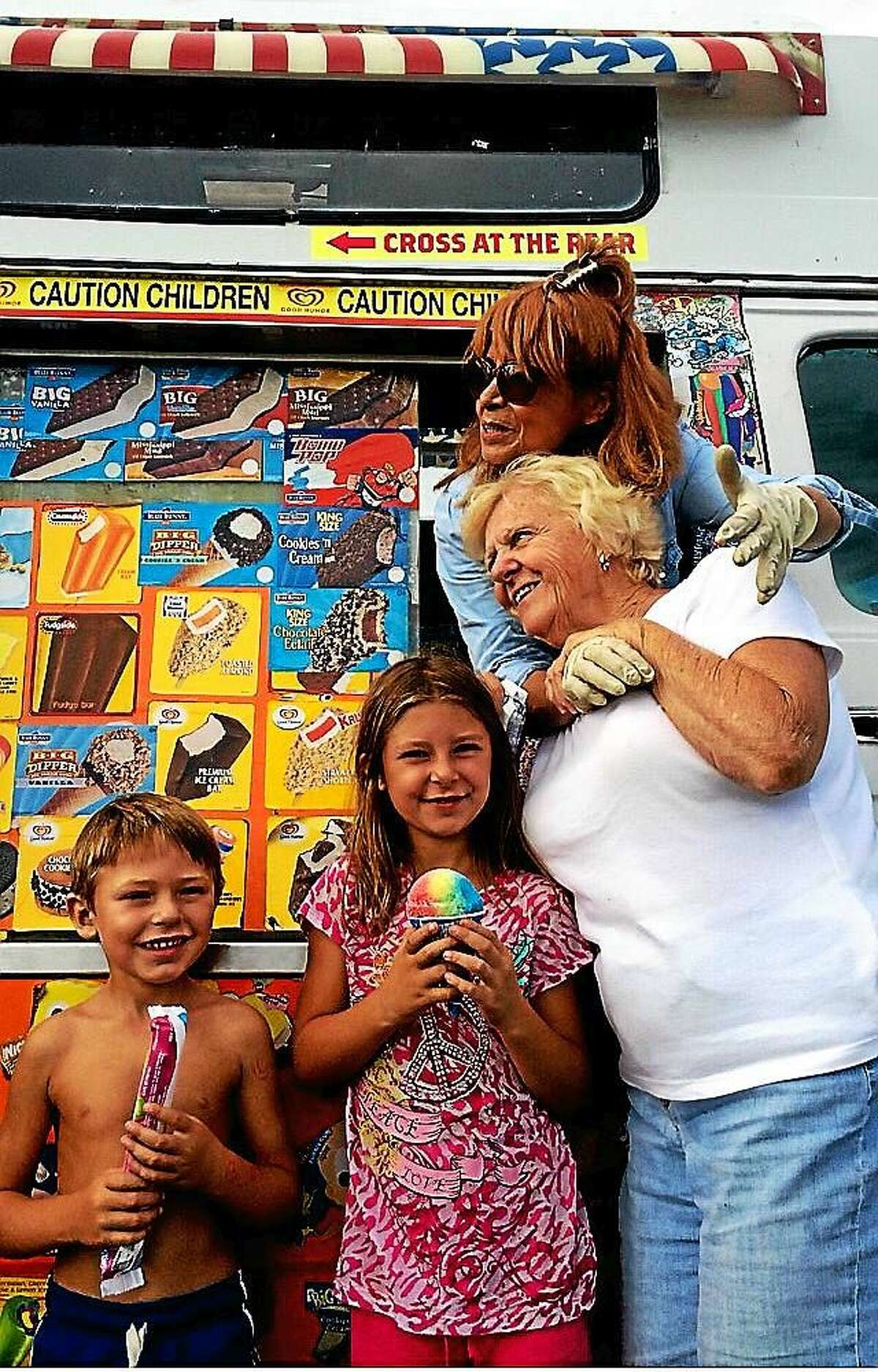 Daisy Gonzalez hugs the matriarch of the Honeyman family, while two younger cousins smile and prepare to eat the frozen treats.