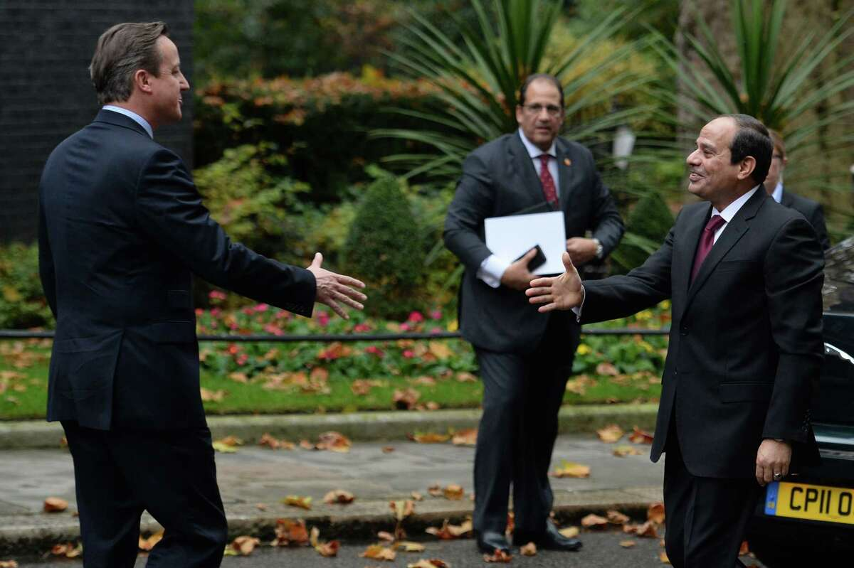 """Britain's Prime Minister David Cameron, left, greets Egyptian president Abdel Fatah el-Sisi at 10 Downing Street in London ahead of their meeting Thursday Nov. 5, 2015. British Prime Minister David Cameron declared Thursday it was """"more likely than not"""" that a bomb brought down a Metrojet flight packed with Russian vacationers — a scenario that officials from Russia and Egypt tried to dismiss as premature speculation. Cameron said he had grounded all flights to and from Egypt's Sinai Peninsula, stranding thousands of British tourists at the Red Sea resort of Sharm el-Sheikh, because of """"intelligence and information"""" indicating that a bomb was the likely culprit in the crash Saturday that killed 224 people."""