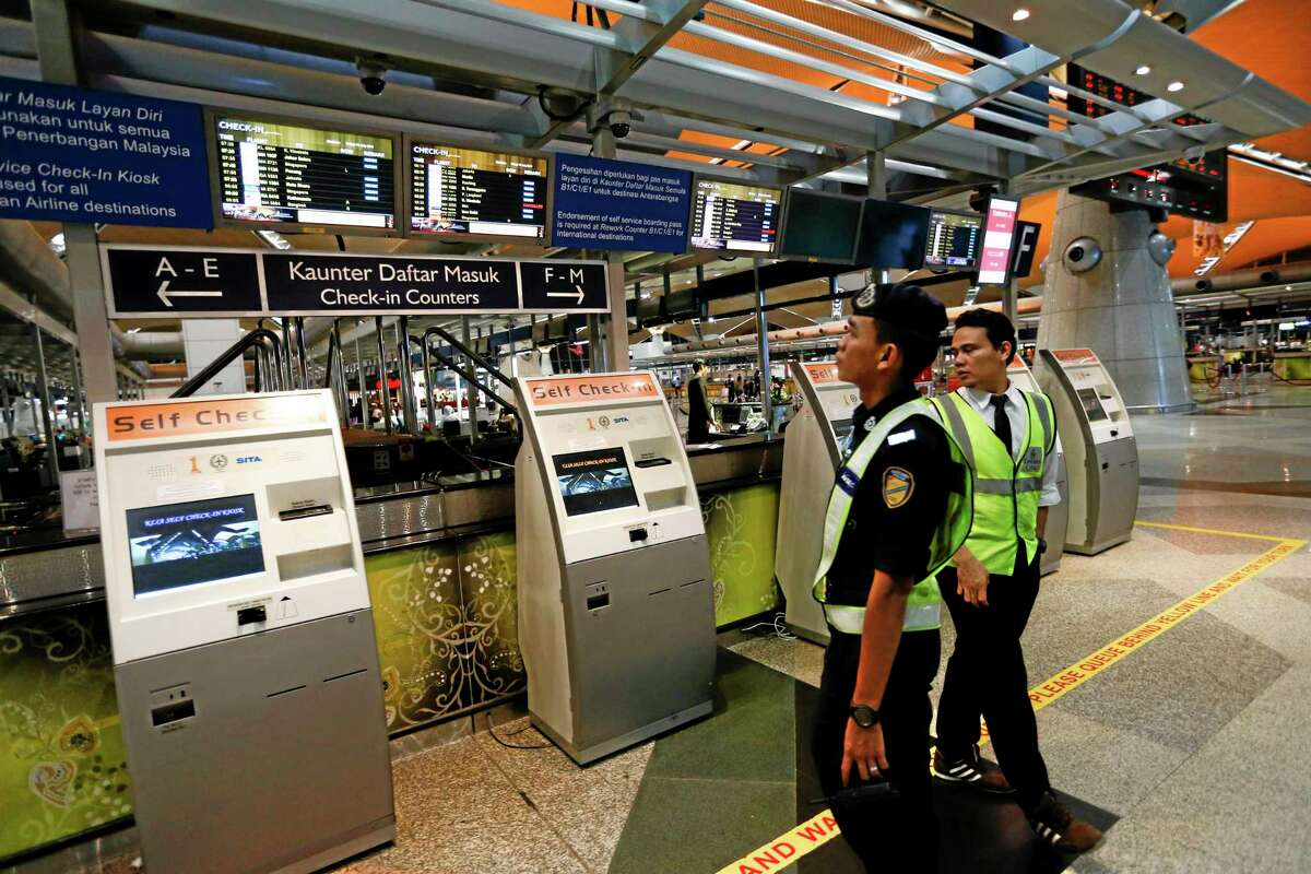 Airport security personnel look at the flight information board in the departure hall, at Kuala Lumpur International Airport, in Sepang, Malaysia, Friday, July 18, 2014. Malaysia Airlines said it lost contact with Flight MH17 over Ukrainian airspace Thursday. It was flying from Amsterdam to Kuala Lumpur, Malaysia. (AP Photo/Vincent Thian)