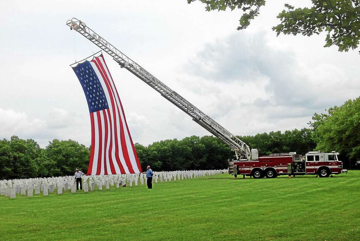 """A large American flag flew from the ladder of Middletown Fire Department's Truck No. 34 during Wednesday's ceremony at the Connecticut Veterans Cemetery where four """"forgotten"""" soldiers were laid to rest."""