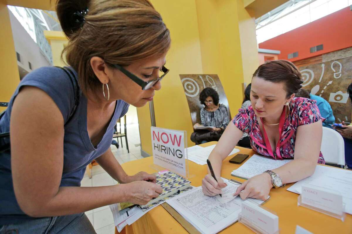 In this Oct. 6, 2015, photo, A'GACI clothing store hiring manager Marcie Lowe, right, gives her card to job applicant Xionara Garcia, left, of Miami, during a job fair at Dolphin Mall in Miami. According to Labor Department statistics released Thursday, Nov. 5, 2015, more Americans applied for unemployment benefits a week earlier, but levels remain near historic lows as employers are hesitant to let go of workers.