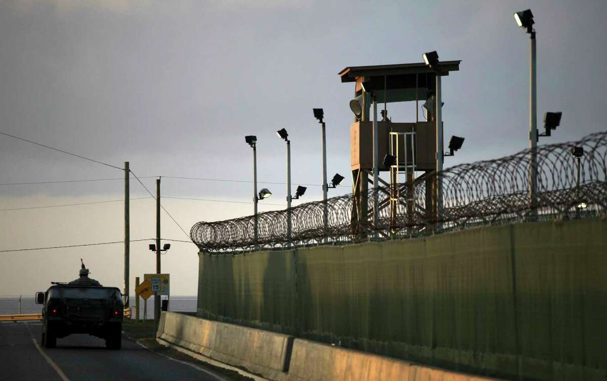 In this March 30, 2010, file photo, reviewed by the U.S. military, a U.S. trooper stands in the turret of a vehicle with a machine gun, left, as a guard looks out from a tower at the detention facility of Guantanamo Bay U.S. Naval Base in Cuba. The House on Thursday overwhelmingly passed a revised $607 billion defense policy bill that restricts President Barack Obama's efforts to close the military prison at Guantanamo Bay, Cuba.