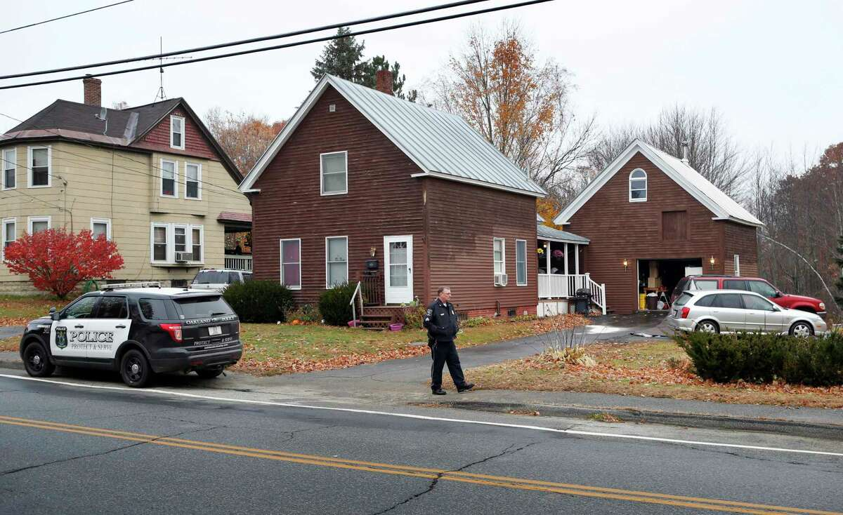 A police officer walks outside a house Thursday, Nov. 5, 2015, where two women and a man were shot to death in Oakland, Maine. Police say the gunman shot himself outside the residence and was found in the driveway.