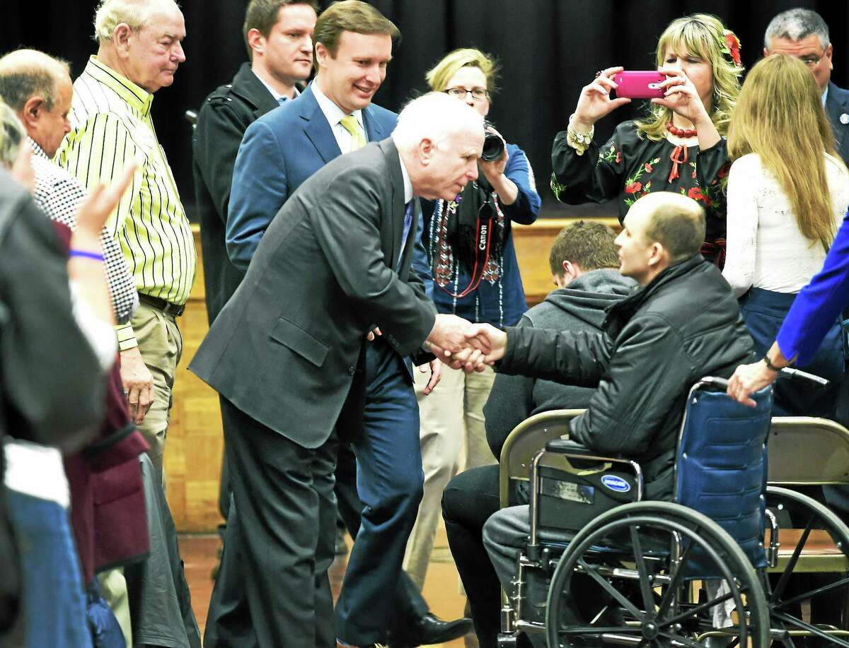 (Peter Hvizdak - New Haven Register) U.S. Senators John McCain shakes hands with Roman Lutsiuk of Ukraine who was wounded in the fighting against pro-Russian insurgents in the Ukraine near the Polish border during a meeting with McCain and U.S. Senator Christopher Murphy and the local Ukrainian community at the Ukrainian National Home in Hartford, Connecticut Monday, March 9, 2015. Lutsiuk is being treated at Yale-New Haven Hospital for injuries sustained in the Ukrainian conflict . The senators held a discussion with the community on the ongoing crisis and the United State's role in supporting the Ukrainian people.