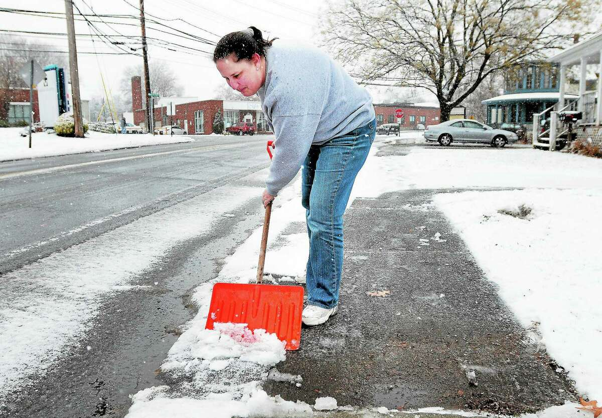 Carol Pooley shovels the sidewalk in front of Pooley Dental Lab on Broad St. in Milford on 12/10/2013.