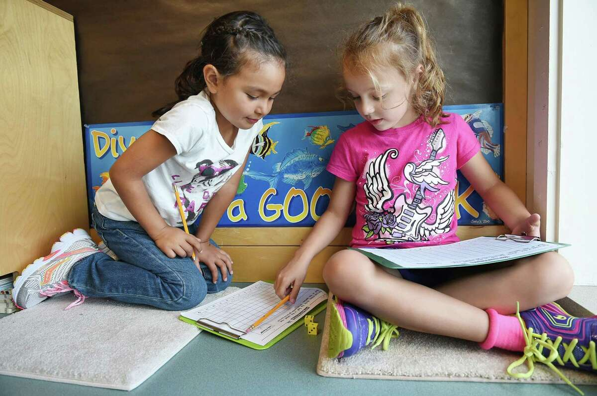 Abby Dahlstrom, 6, left, and Caitlin Burgess, 7, use dice during their math class on the first day of school in Jill Garrity's second grade class at Bielefield Elementary School in this 2014 file photo.