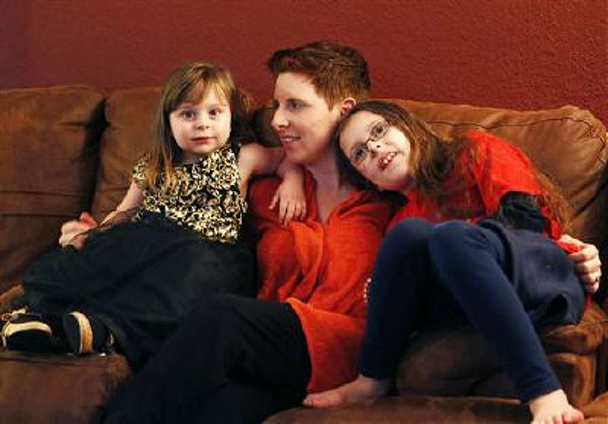 Melanoma survivor Jodi Duke, center, sits with her daughters Zoe, left, 3, and Violet, 8, at home in Aurora, Colo.