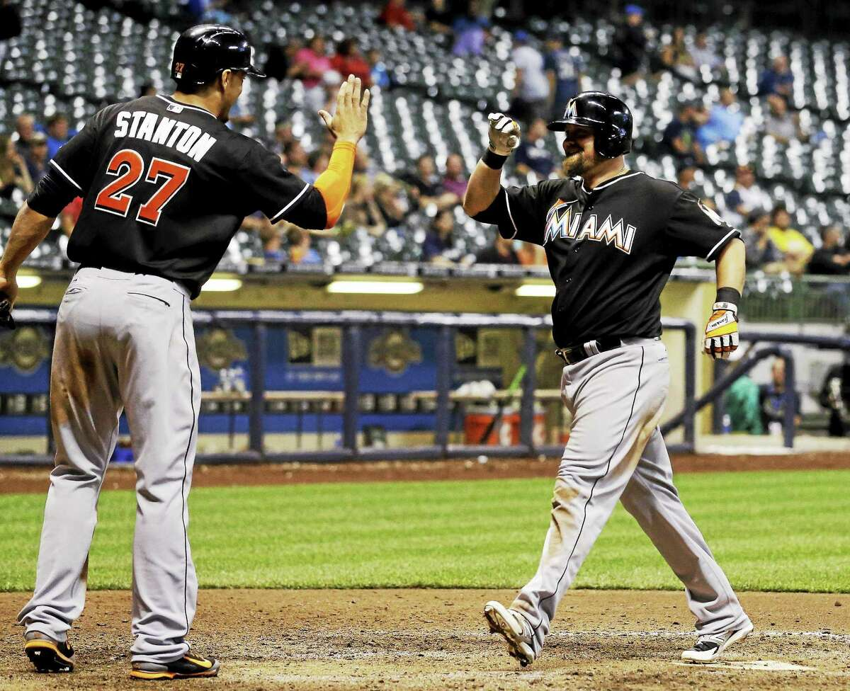 Miami's Casey McGehee is congratulated by Marlins teammate Giancarlo Stanton after McGehee hit a two-run home run during the ninth inning of a Sept. 9 game against the Brewers in Milwaukee.