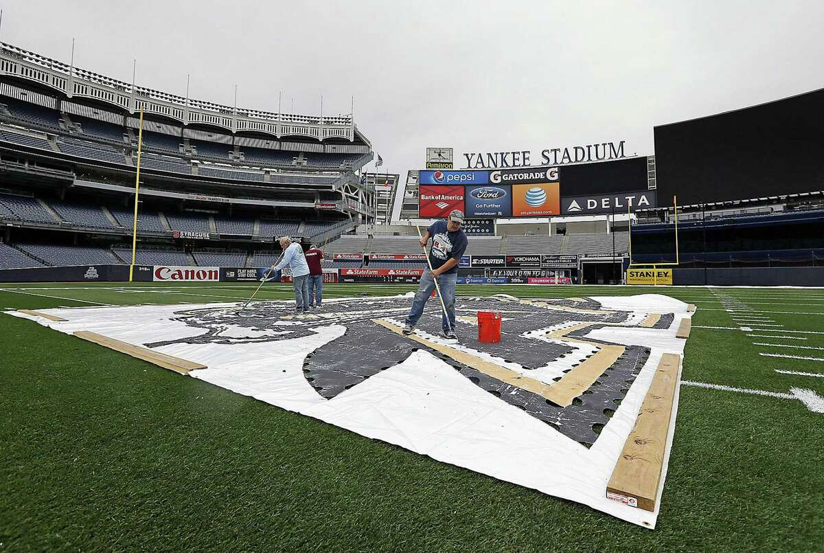 Grounds crew workers paint the Army Black Knights logo on the turf at midfield on Wednesday at Yankee Stadium in New York.