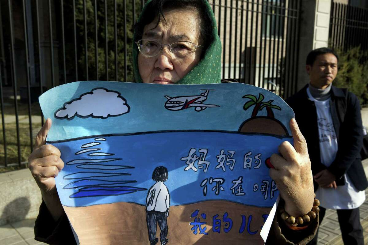 """A woman whose son was on board the missing Malaysia Airlines Flight 370 protests with a banner which reads """"Mother's heart is broken, where are you my son"""" near the Malaysian Embassy in Beijing on the one year anniversary, Sunday."""