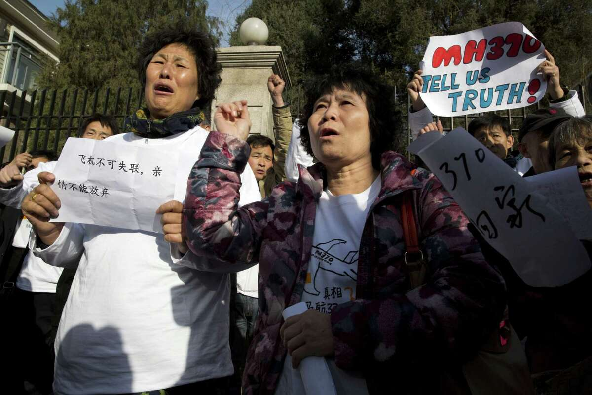 Relatives of passengers onboard the missing Malaysia Airlines Flight 370 protest near the Malaysian embassy in Beijing on the one year anniversary Sunday.