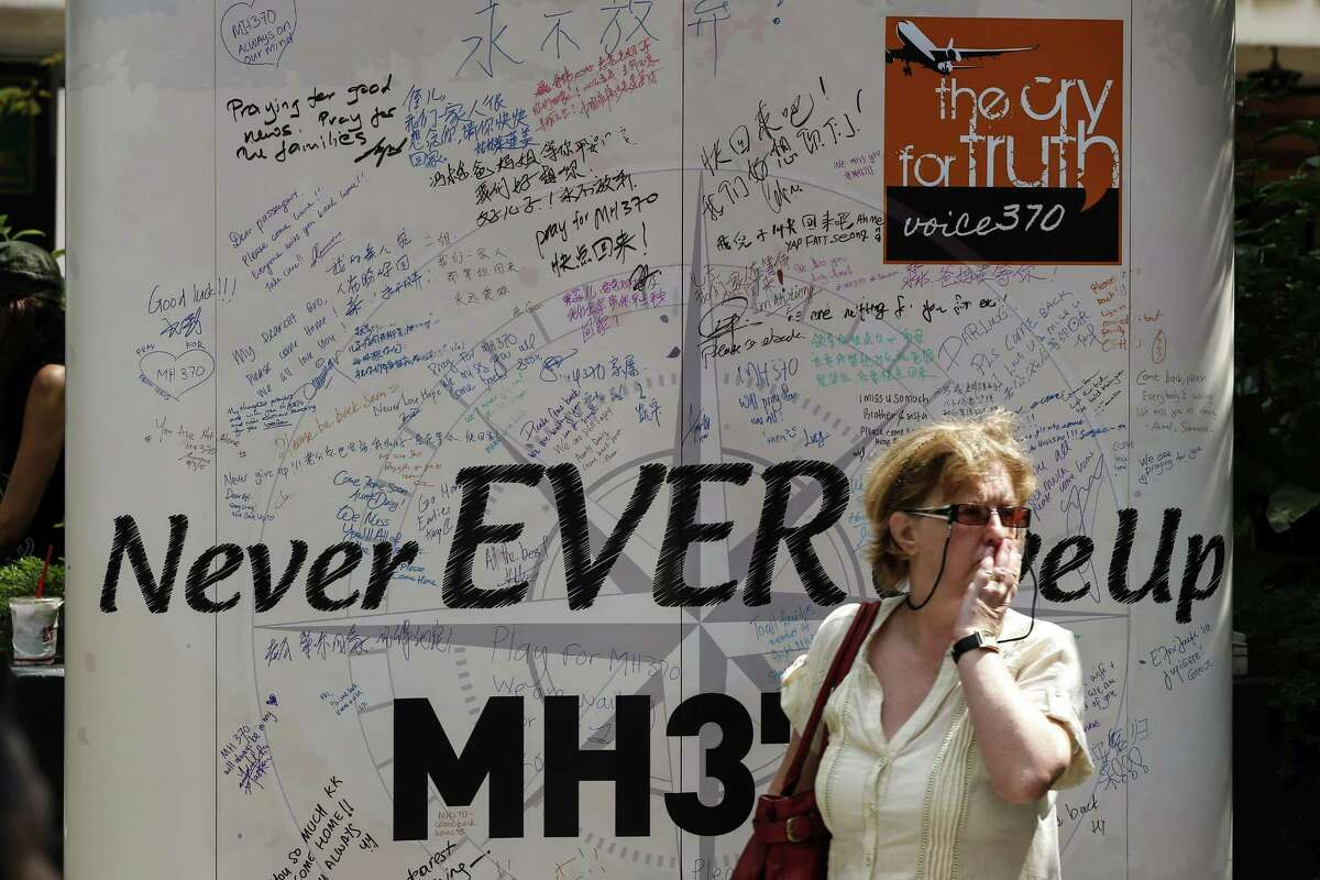 A visitor walks past a board with well-wishing messages during a remembrance event in a mall outside Kuala Lumpur, Malaysia Sunday.