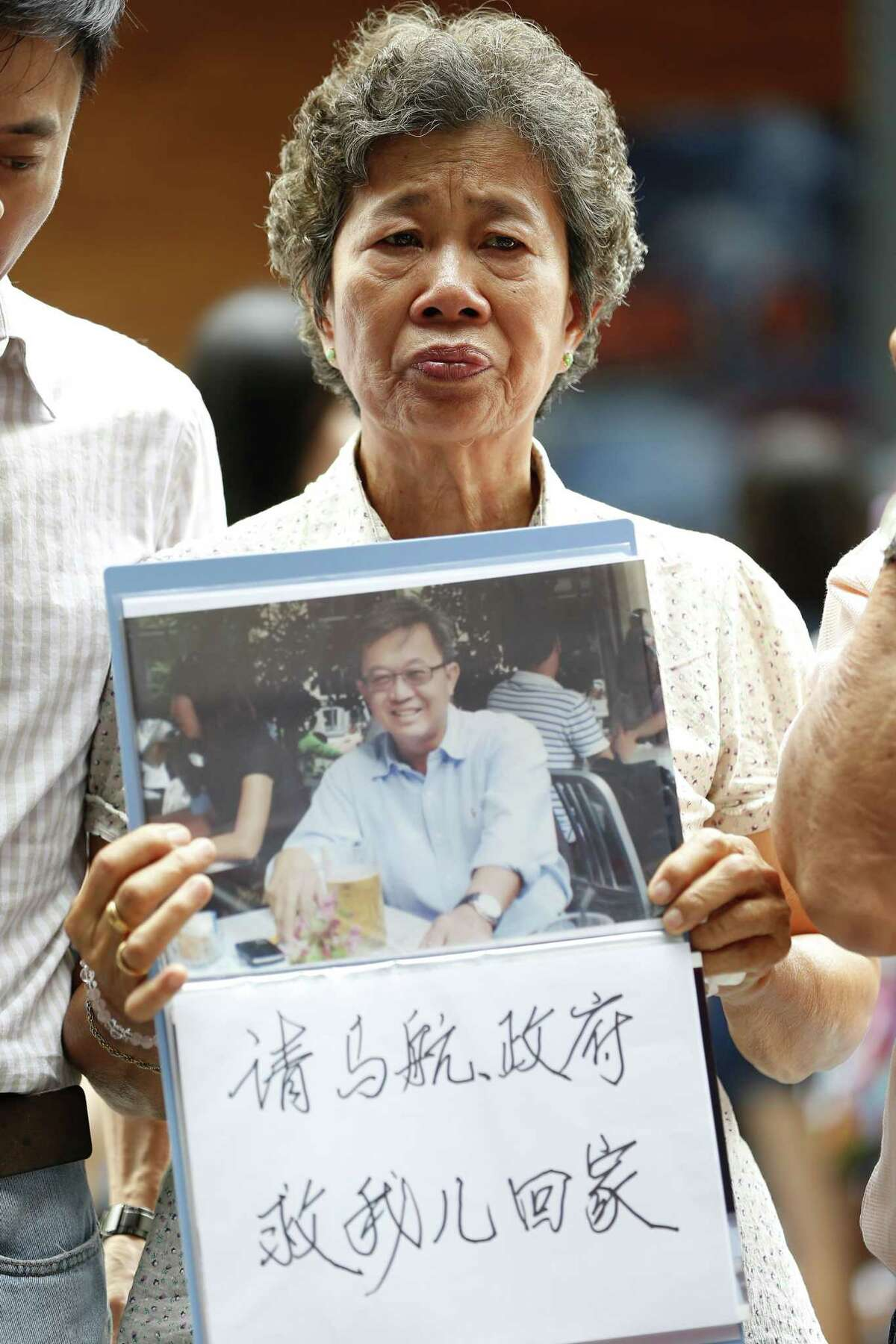 Malaysia's Madam Wong holds a message and a photo of her son, Tan Chong Ling, who was a passenger on board the ill fated Malaysia Airlines Flight 370, during a remembrance event in a mall outside Kuala Lumpur, Malaysia Sunday.