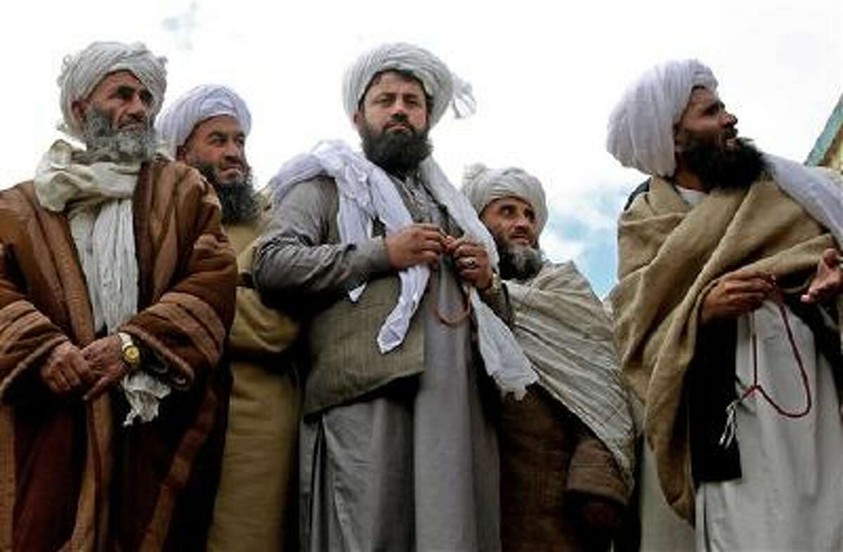 Afghan men gather Monday after an explosion hit a school yard in eastern Kabul, Afghanistan.