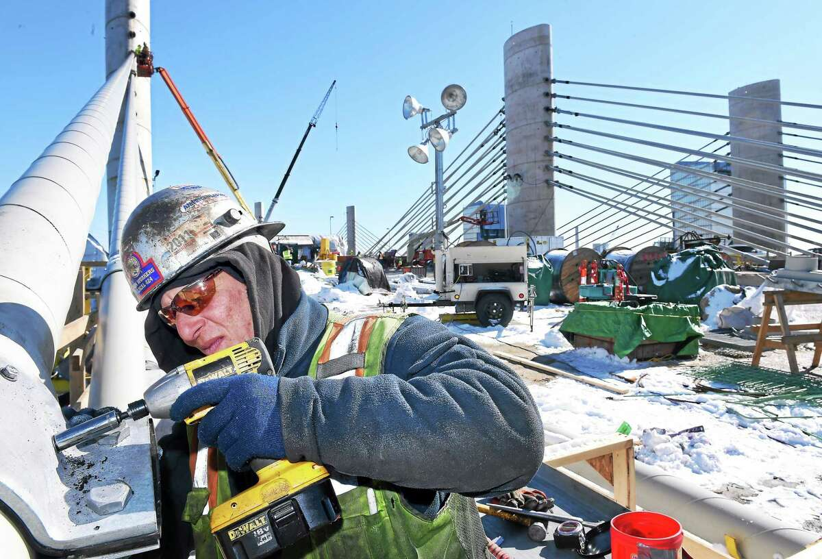 ARNOLD GOLD — NEW HAVEN REGISTER Michael Shaw installs bolts on a collar for the stay cable dampeners on the Pearl Harbor Memorial Bridge in New Haven on Friday.