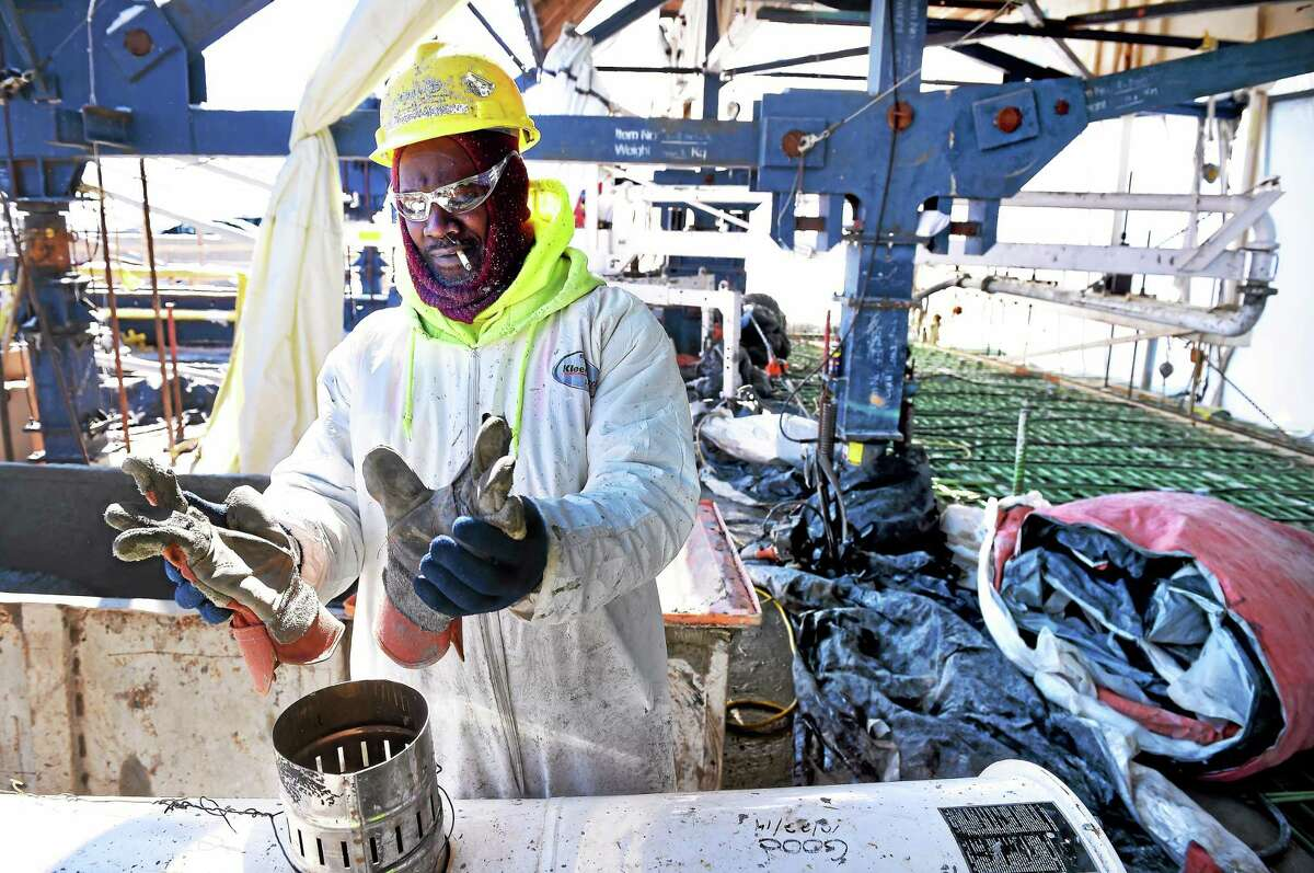 ARNOLD GOLD — NEW HAVEN REGISTER Harrison Green warms his gloves while pouring concrete on a segment of the Pearl Harbor Memorial Bridge in New Haven on Friday.
