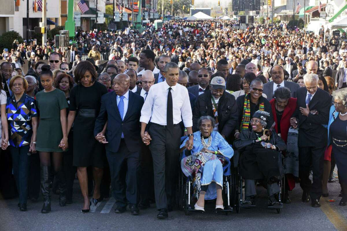 """President Barack Obama, center, walks as he holds hands with Amelia Boynton, who was beaten during """"Bloody Sunday,"""" as they and the first family and others including Rep. John Lewis, D-Ga,, left of Obama, walk across the Edmund Pettus Bridge in Selma, Ala. for the 50th anniversary of """"Bloody Sunday,"""" a landmark event of the civil rights movement Saturday. From front left are Marian Robinson, Sasha Obama and first lady Michelle Obama."""