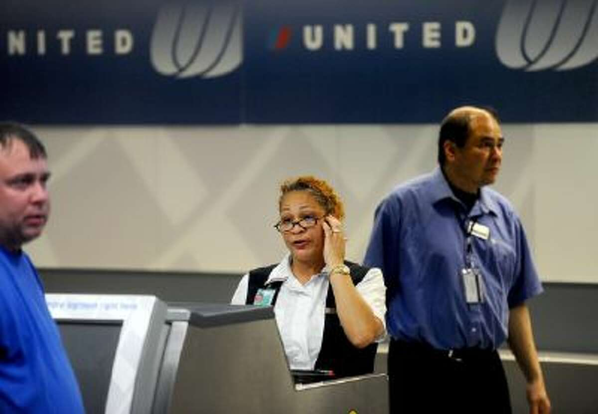 n this Friday, June 17, 2011, file photo, a United Airlines employee staffs a ticketing counter at San Francisco International Airport, in San Francisco. United Airlines said, Jan. 16, 2014, it will furlough 688 flight attendants after it didn't get enough people to take a voluntary buyout