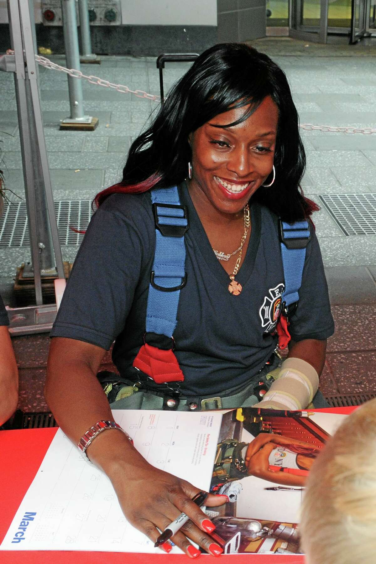 In a photo provided by the New York City Fire Department, firefighter Danae Mines autographs a copy of the 2015 Calendar of Heroes, which features her as Miss March, Tuesday, July 15, 2014, in New York's Times Square. Mines, of Engine Co. 6 in the South Bronx, is an 11-year veteran, one of only 41 female firefighters in the department, and the first female firefighter to appear in the famed charity calendar of hard bodies. (AP Photo/FDNY)