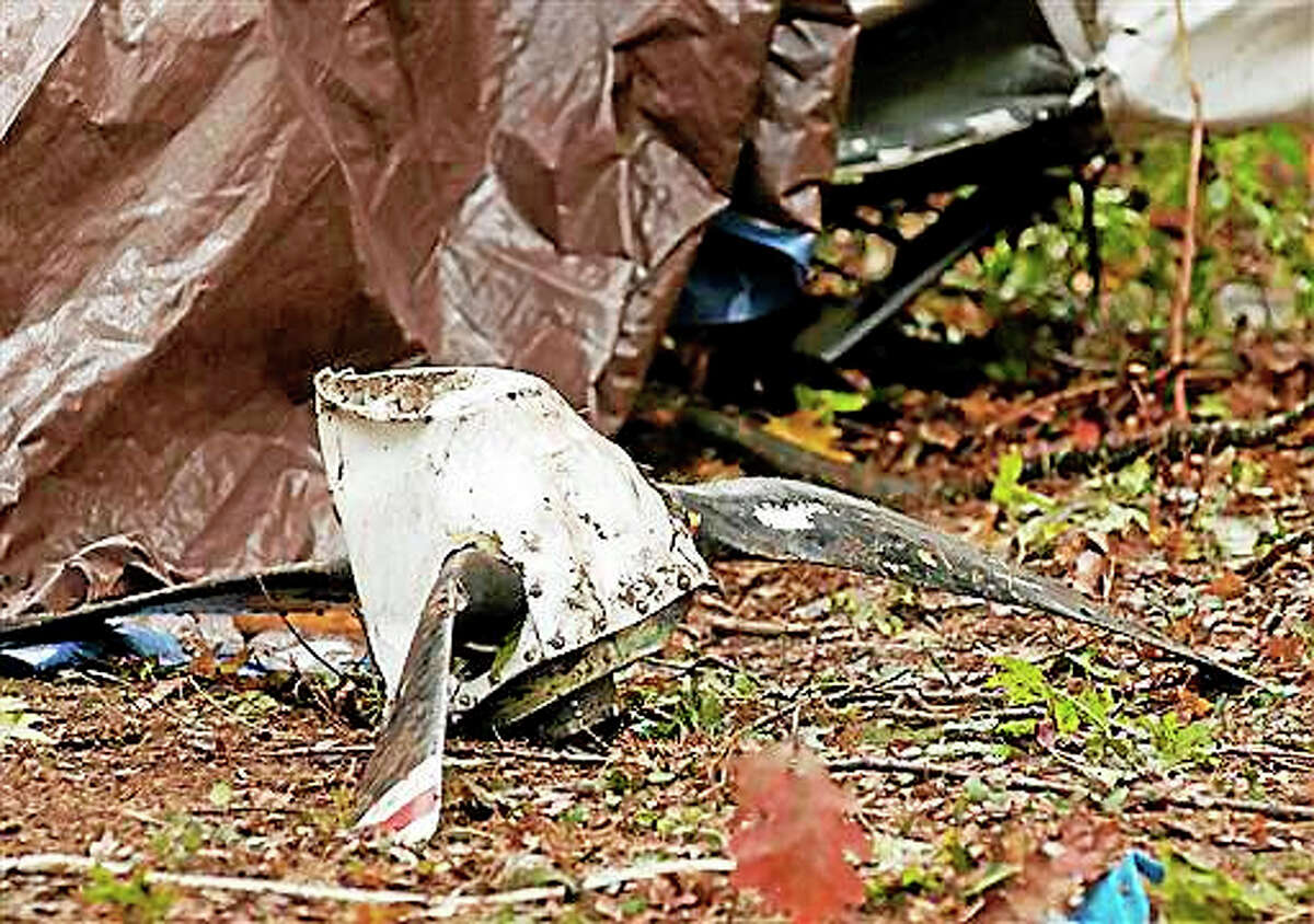 A damaged propeller sits among the wreckage of a single-engine airplane in woods near the Worcester Municipal Airport in Worcester, Mass. Sunday, Oct. 25, 2015. Worcester District Attorney Joseph Early says Putnam, Connecticut, resident Gary Weller was the only person on the 1996 Mooney M20M when it crashed Saturday morning. The 66-year-old Weller was pronounced dead at the scene.