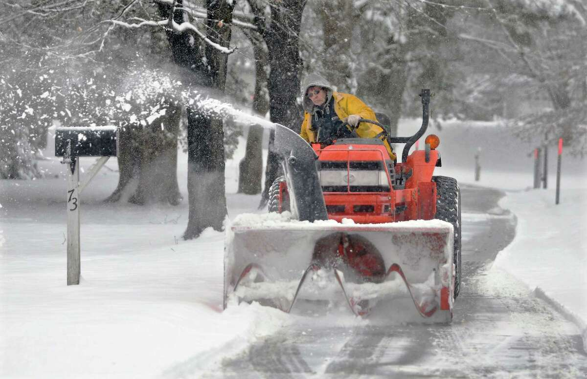 Debbie Smoloski clears the snow off her 655-foot-long driveway in Middletwon using her Kubota L3010 Monday afternoon. Smoloski said it will take her about an hour and a half to plow her driveway, then she'll move on to her parents' and aunt's shared driveway.