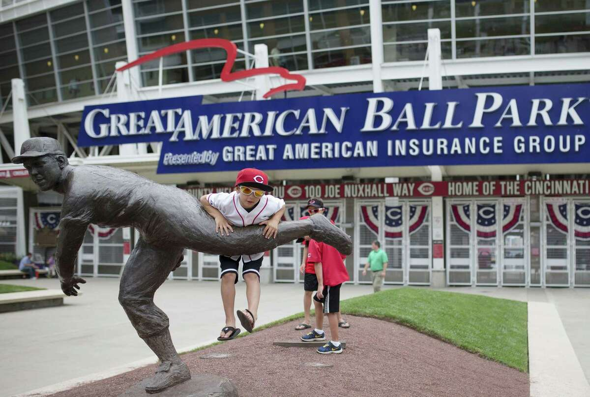 Conner Schreck, of Cincinnati, plays on a statue of former Cincinnati Reds baseball player Joe Nuxhall outside Great American Ball Park on Monday. The Reds are hosting the All-Star Game for the first time since 1988.