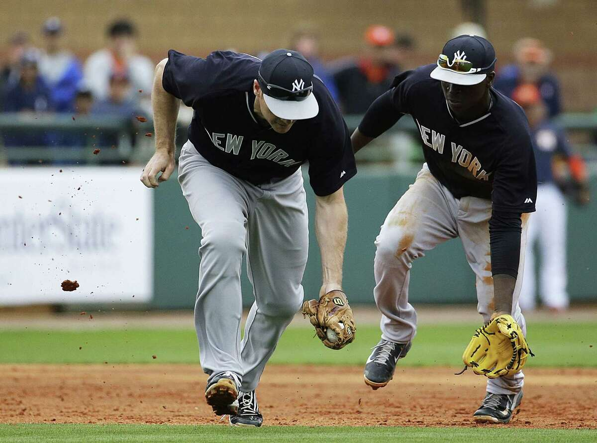 New York Yankees third baseman Chase Headley, left, fields a groundout by the Houston Astros' Hank Conger while being backed up by teammate Didi Gregorius during Saturday's game in Kissimmee, Fla.