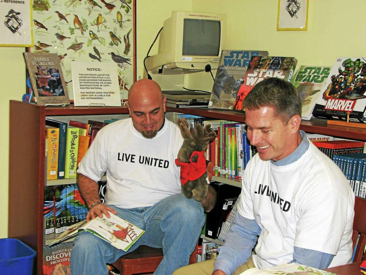 Volunteers from GKN Aerospace Services Structures read with children at the Acton Public Library in Old Saybrook as part of Middlesex United Way's annual Day of Caring. More than 40 volunteers from nine companies participated in Day of Caring projects in seven Middlesex County towns during October and November.