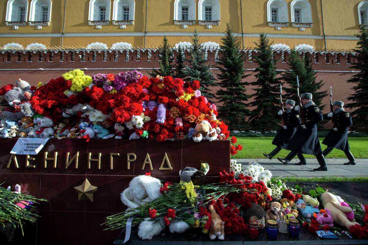 The Kremlin guards pass flowers and toys laid at the memorial stone with the word Leningrad (St. Petersburg) at the Tomb of the Unknown Soldier outside Moscow's Kremlin Wall in Moscow, Russia, Tuesday, Nov. 3, 2015. Mourners have been coming to St. Petersburg's airport and other places since Saturday with flowers, pictures of the victims, stuffed animals and paper planes. Metrojet's Airbus A321-200 en route from Egypt's Sharm el-Sheikh to St. Petersburg crashed over the Sinai Peninsula on Saturday, killing all 224 on board.