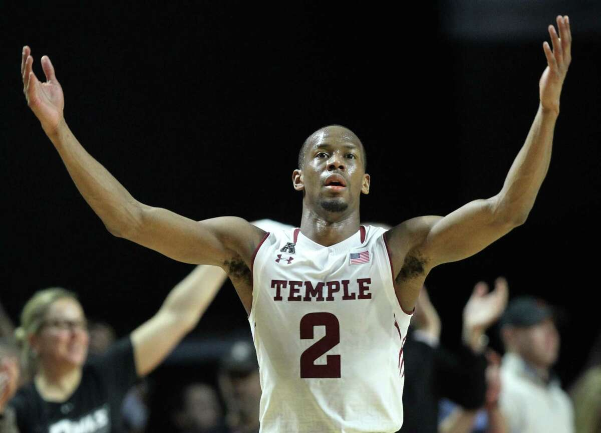 Temple guard Will Cummings raises his hands to celebrate after the Owls defeated UConn 75-63 on Saturday in Philadelphia.