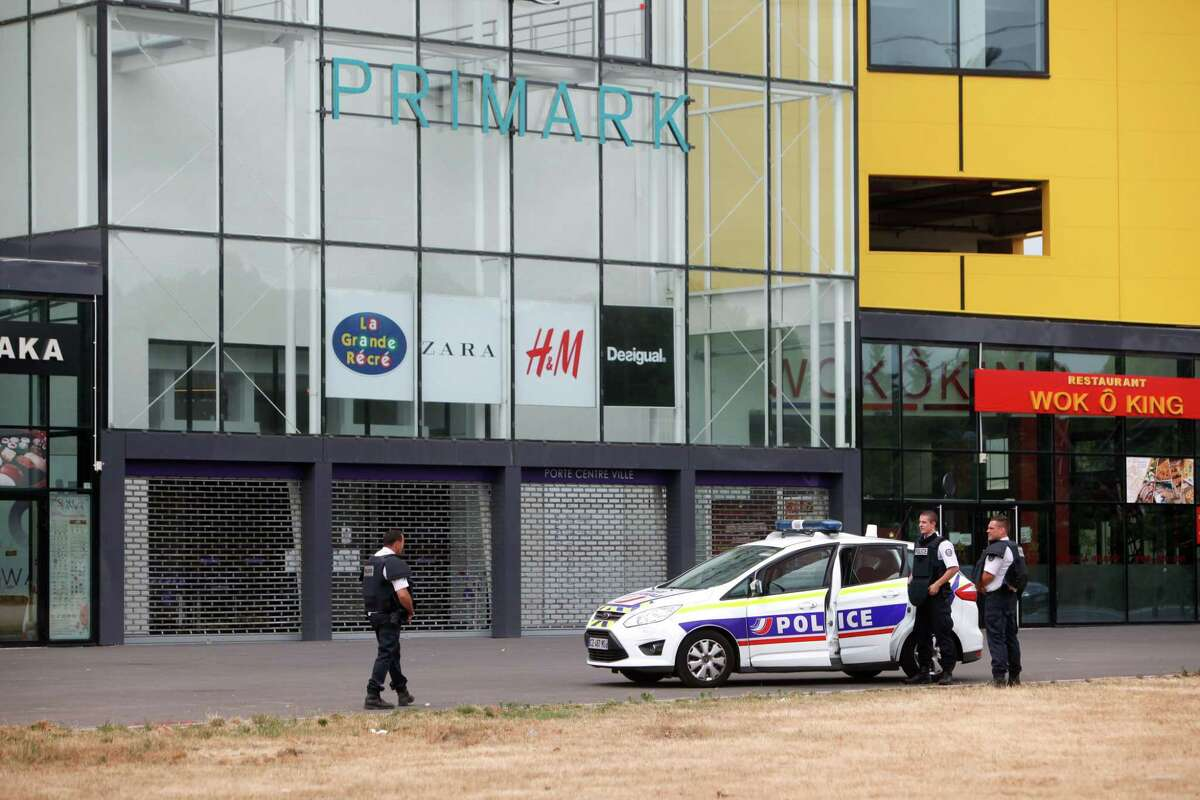 Police officers stand outside a suburban clothing store, in Villeneuve-la-Garenne, north of Paris, Monday. A group of assailants broke into the Primark discount clothing store in the town of Villeneuve-la-Garenne early Monday and several employees were trapped inside, police said.