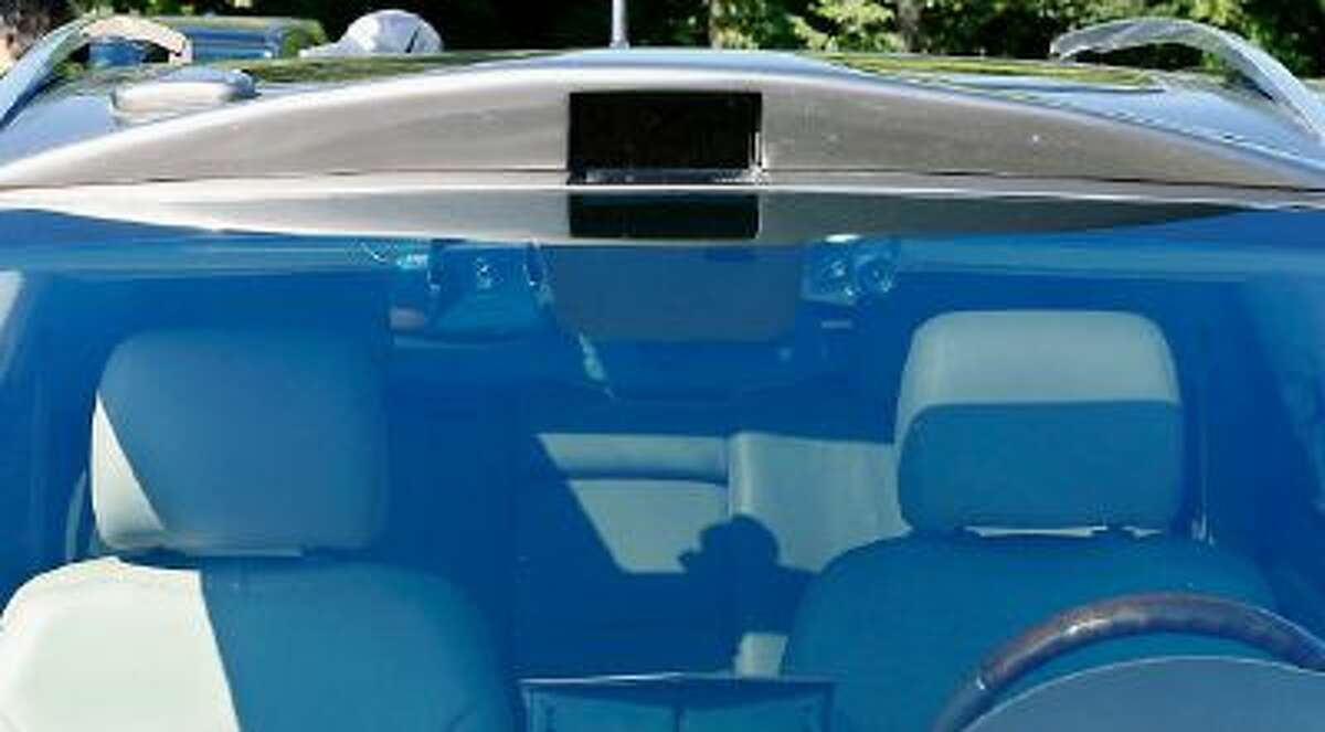 An Infrared sensor is seen above the windshield and two cameras are also seen beside the rear-view mirror of this Cadillac SRX that was modified by Carnegie Mellon University.