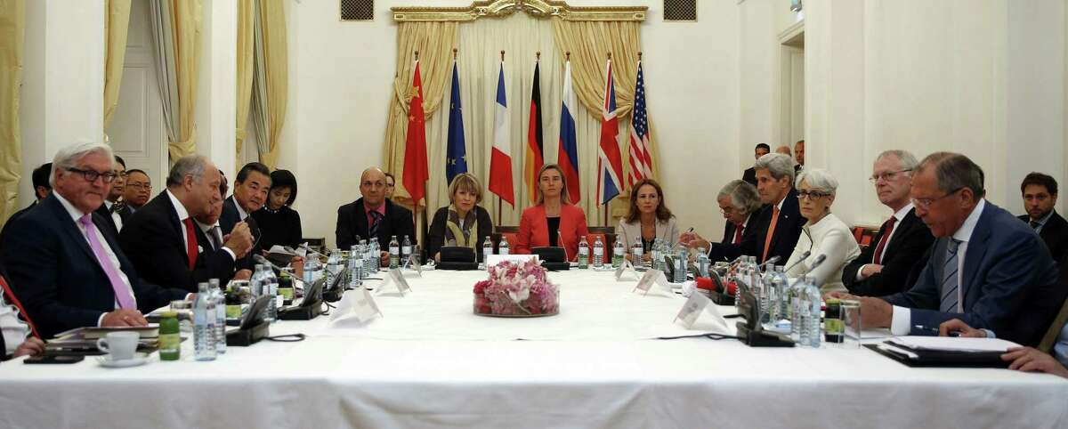 German Foreign Minister Frank-Walter Steinmeier, left, French Foreign Minister Laurent Fabius, 2nd left, Chinese Foreign Minister Wang Yi, 3rd left, European Union foreign policy chief Federica Mogherini, centre in red, U.S. Secretary of State John Kerry, 4th right, and Russian Foreign Minister Sergei Lavrov, right, meet at a hotel in Vienna Monday.