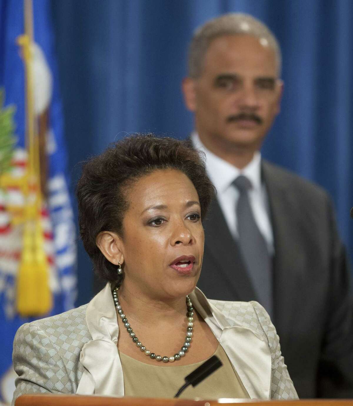 In this July 28, 2014 file photo, Attorney General Eric Holder, right, listens to, Loretta Lynch, left, U.S. Attorney for the Eastern District of New York speaks during a news conference at the Justice Department in Washington. President Obama chose Lynch as attorney general on Friday, Nov. 7, 2014, which would make her the first black woman in the position