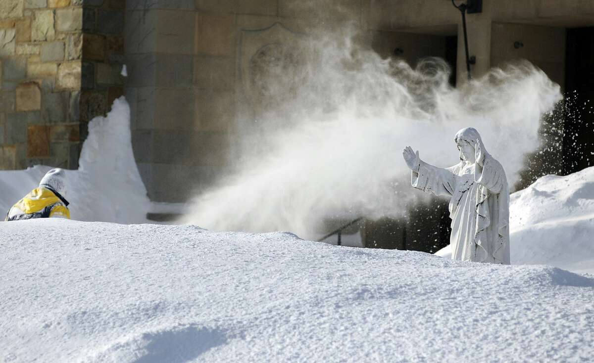 In this Feb. 16 file photo, custodian George Blomquist clears snow from the grounds of Our Lady of the Angels Church after a weekend snowstorm in Worcester, Mass. Churches, synagogues and mosques in New England report that attendance is down at worship services this winter, as many storms have hit the region.