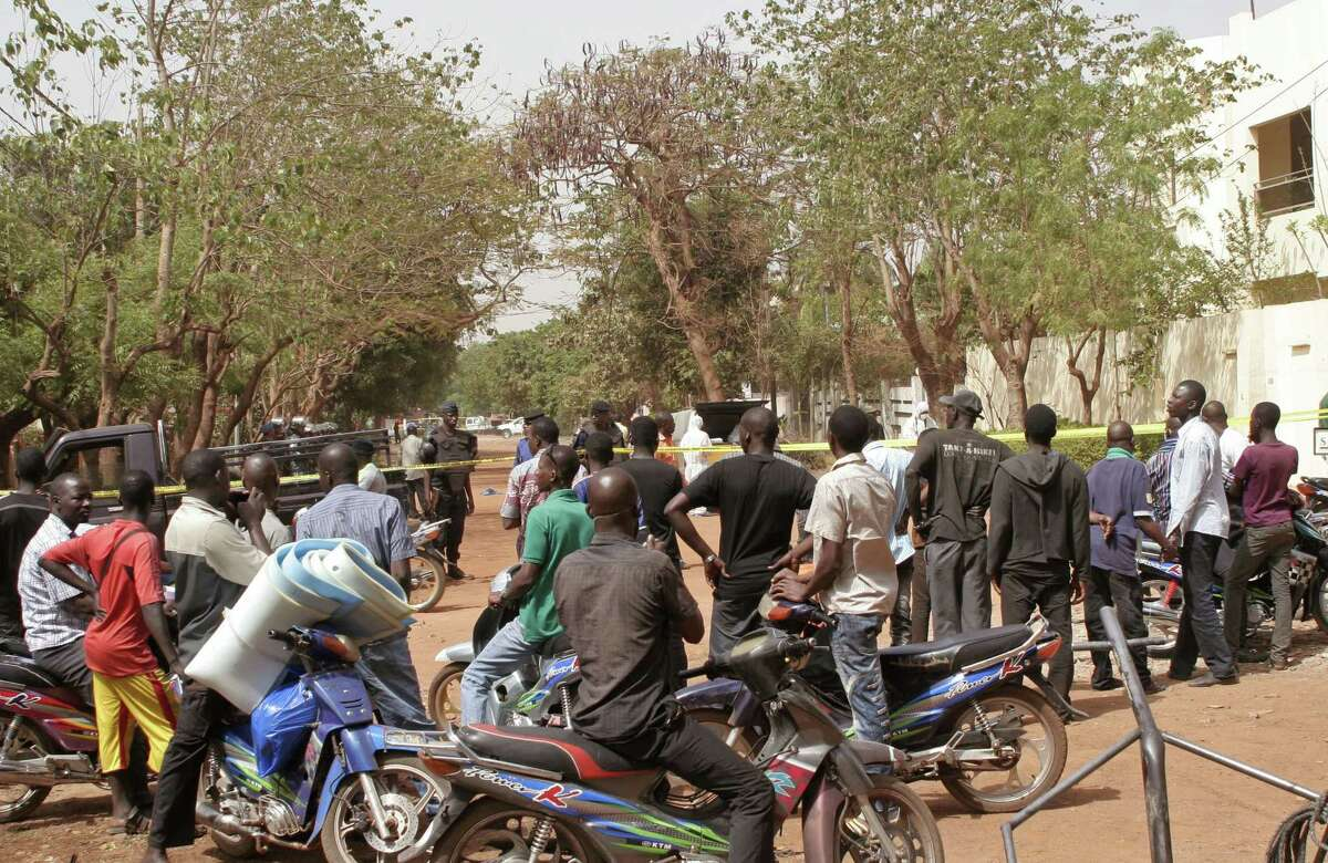 Local residence gather in the street leading to a nightclub that was attacked by gunmen in Bamako, Mali, Saturday, March 7, 2015. A masked gunman sprayed bullets around a nightclub popular with foreigners in Maliís capital early Saturday, killing at least five people including a French person and a Belgian national, officials and witnesses said. (AP Photo/Harouna Traore)