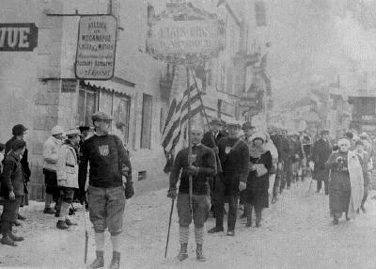 In this Jan. 25, 1924, file photo, a man carries the American flag, as the United States is represented during opening ceremonies for the I Winter Olympics in Chamonix, France.