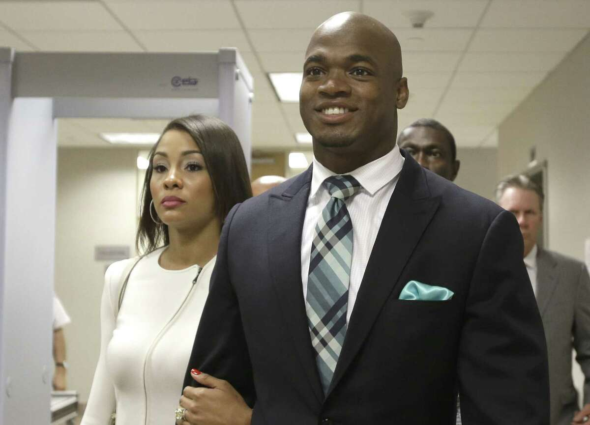 Minnesota Vikings running back Adrian Peterson leaves the courthouse with his wife, Ashley Brown Peterson, on Tuesday in Conroe, Texas.