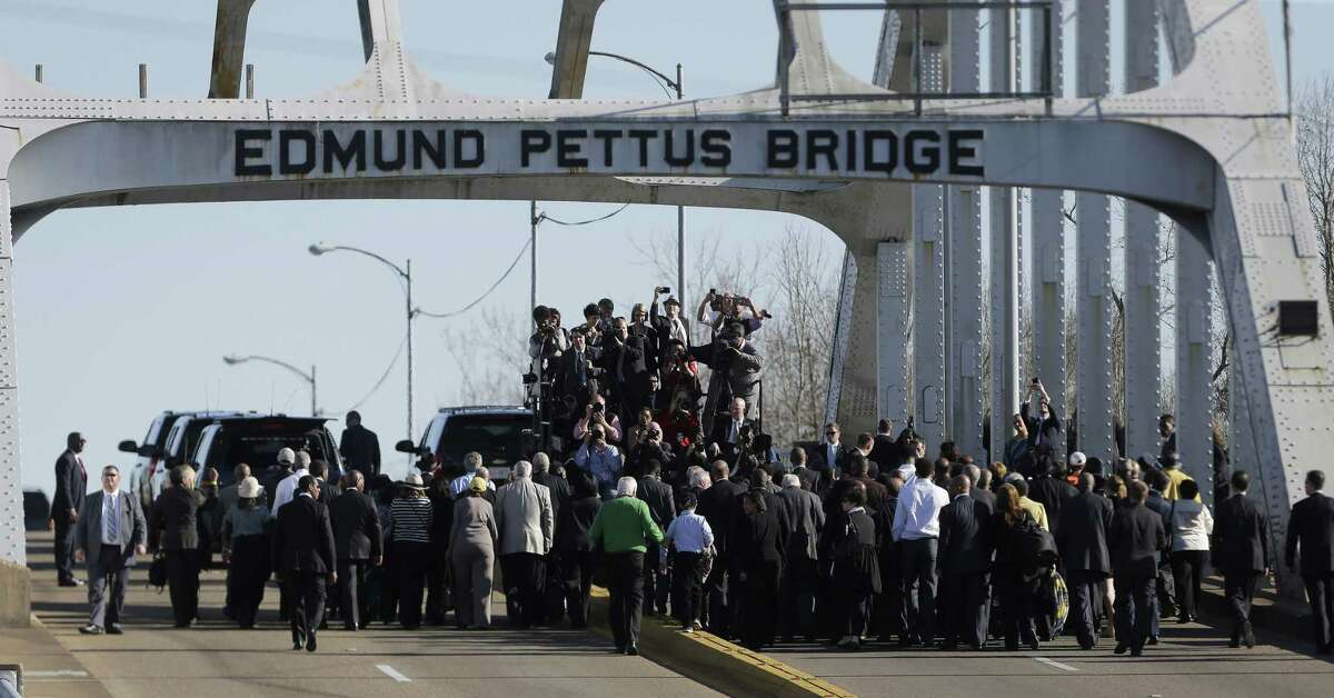 """President Barack Obama, first lady Michelle Obama, Malia and Sasha as well as members of Congress and civil rights leaders make a symbolic walk across the Edmund Pettus Bridge, Saturday, March 7, 2015, in Selma, Ala. This weekend marks the 50th anniversary of """"Bloody Sunday,' a civil rights march in which protestors were beaten, trampled and tear-gassed by police at the Edmund Pettus Bridge, in Selma. (AP Photo/Gerald Herbert)"""