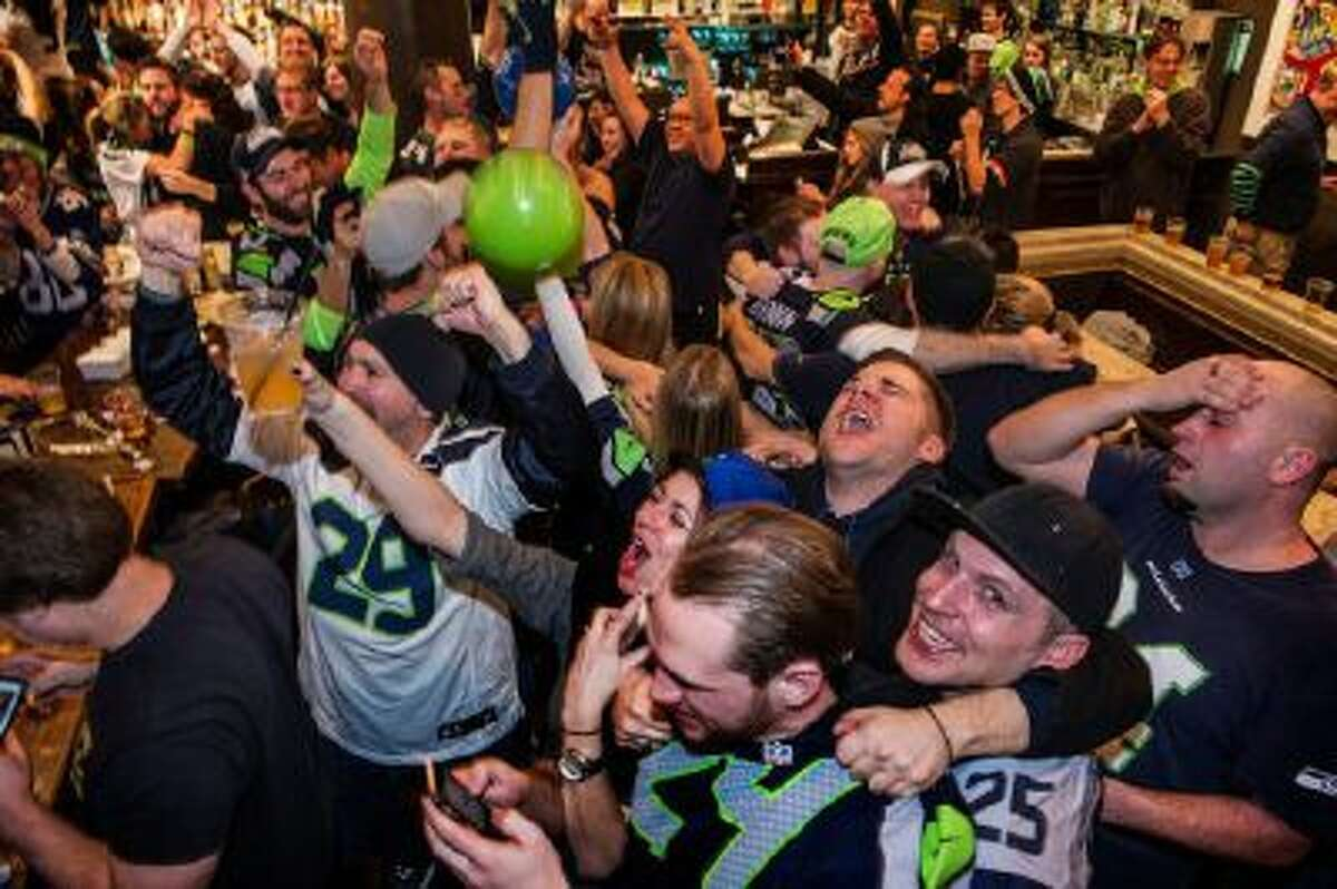 Seattle Seahawks fans celebrate their team's victory over the Denver Broncos in Super Bowl XLVIII at a downtown sports bar in Seattle Sunday.