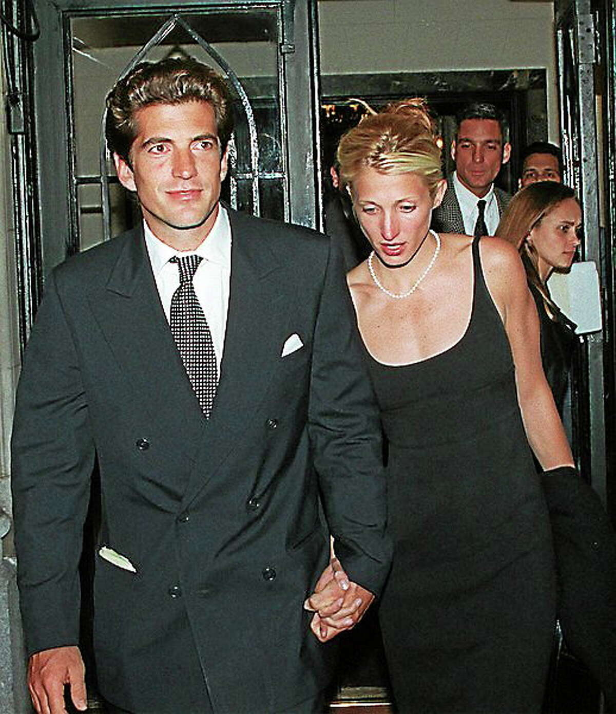John F. Kennedy Jr. and his new bride Carolyn Bessette-Kennedy walk out hand-in-hand from a party and Kennedy family gathering in New York late Thursday night, Oct. 10, 1996.