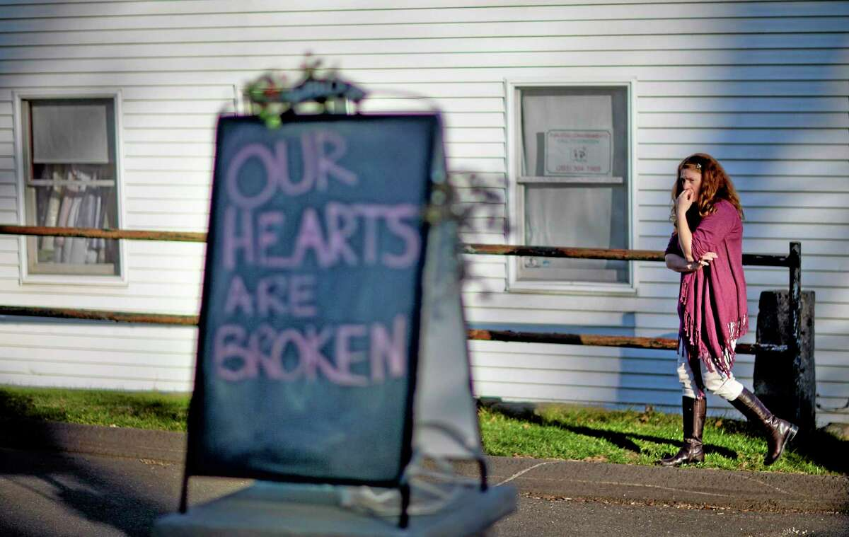 FILE - In this Dec. 15, 2012 file photo, shop owner Tamara Doherty paces outside her store just down the road from Sandy Hook Elementary School in Newtown, Conn. Although still relatively rare, thereís been no real reduction in the number of school shootings since security was beefed up around the country with measures such as safety drills and the hiring of police officers. (AP Photo/David Goldman, File)