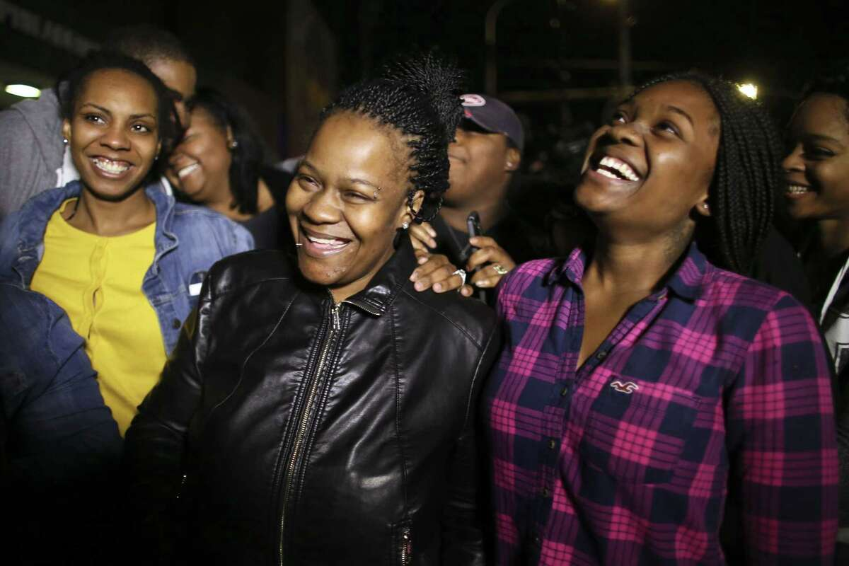 Family members surround Keisha Gaither, second from left, mother of kidnapping victim Carlesha Freeland-Gaither, as they celebrate following a news conference in Philadelphia on Tuesday Nov. 5, 2014, where investigators announced the woman seen on a surveillance video being abducted by a man off a Philadelphia street has been found safe outside Baltimore. Carlesha Freeland-Gaither was found in Jessup, Maryland, and the man who took her was arrested, police said Wednesday.
