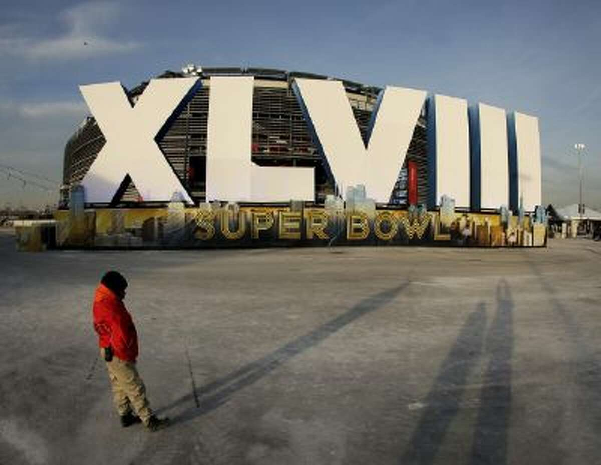 A security guard stands by a sign for NFL football's Super Bowl XLVIII stands in front of MetLife Stadium Saturday in East Rutherford, N.J. The stadium will be the site of Sunday's championship game between the Denver Broncos and the Seattle Seahawks.