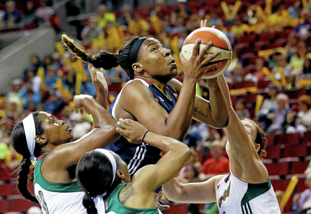The Sun's Kelsey Bone, center, comes down with a rebound in a crowd of Storm players during the first half of Connecticut's 86-63 win on Tuesday in Seattle.