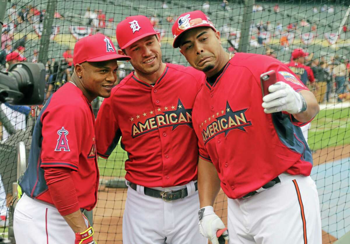 American League's Nelson Cruz, right, of the Baltimore Orioles, takes a photo with fellow American League teammates Ian Kinsler, center, of the Detroit Tigers and Erick Aybar of the Los Angeles Angels during batting practice before the MLB All-Star baseball game, Tuesday, July 15, 2014, in Minneapolis. (AP Photo/Jim Mone)