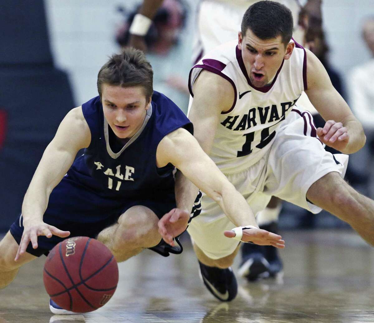 Yale guard Makai Mason, left, and Harvard guard Corbin Miller scramble for a loose ball during the first half of the Bulldogs' 62-52 win on Friday night in Cambridge, Mass.