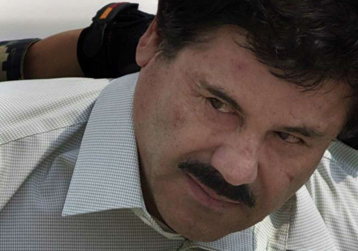 """In this Feb. 22, 2014 file photo, Joaquin """"El Chapo"""" Guzman is escorted to a helicopter in handcuffs by Mexican navy marines at a navy hanger in Mexico City. Mexico's security commission says top drug lord Joaquin 'El Chapo' Guzman has escaped from a maximum security prison for the second time."""